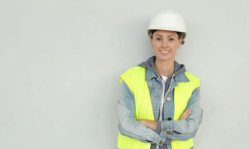 Builderstorm-Smiling female construction worker in safety gear on grey backgr
